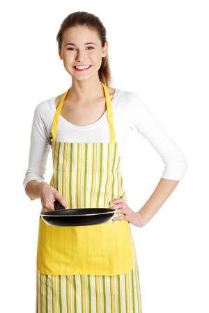 Vooraanzicht portret van een lachende jonge blanke vrouw tiener gekleed in schort, met een pan in de voorkant van haar, op wit. Stockfoto