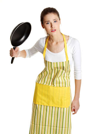 Front view portrait of a young angry caucasian female teen dressed in apron, trying to hit with a frying pan, on white. photo
