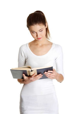 Front view portrait of a beautiful young caucasian teen reading a Bible, on white. photo