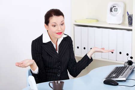 Pretty caucasian businesswoman gesturing don`t know what to do. photo