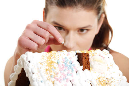 Young woman decorating gingerbread house model Stock Photo - 12388308