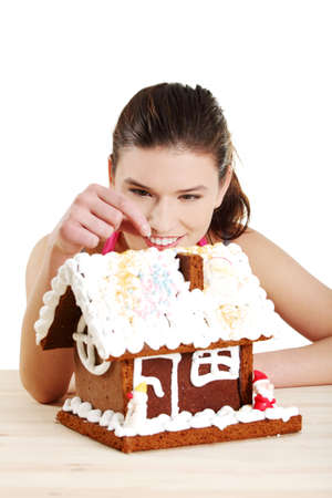 Young woman decorating gingerbread house model photo