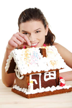Young woman decorating gingerbread house model Stock Photo - 12388339