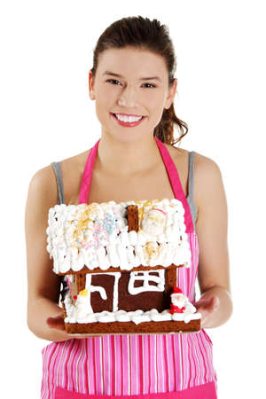 Young woman holding gingerbread house model, isolated on white background photo