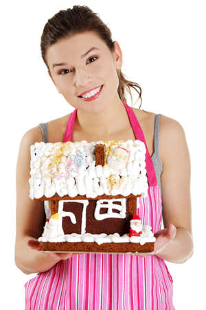 Young woman holding gingerbread house model, isolated on white background Stock Photo - 12388354