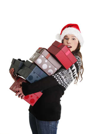 Young woman in santa hat holding christmas boxes, isolated on white background.