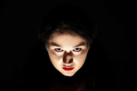 succubus: Scary portrait of angry woman against black background  Stock Photo