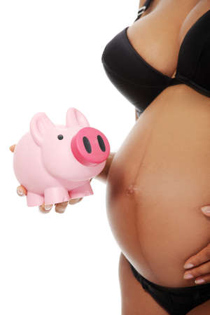 Site vierw belly closeup of a young beautiful pregnant woman holding a pink piggybank next to her belly, over a white background. Stock Photo - 12111580