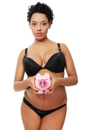 Site vierw of a young beautiful pregnant woman holding a pink piggybank next to her belly, isolated on a white background. photo