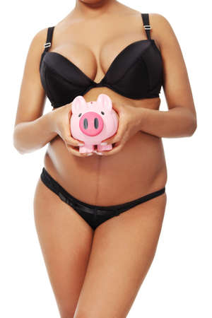 Front vierw of a young beautiful pregnant woman holding a pink piggybank in front of her belly, over a white background. photo