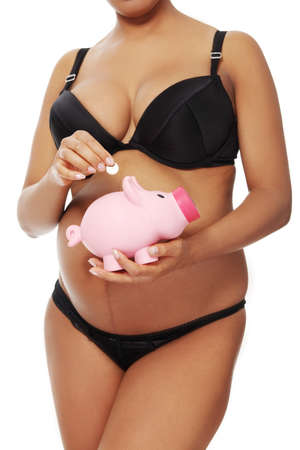 Front vierw of a young beautiful pregnant woman throwing a coin into a pink piggybank holding in front of her belly, over a white background. photo