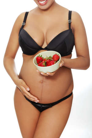 Front vierw portrait of a young beautiful pregnant woman holding a salad-bowl of strawberries in front of her tummy, over a a white background. photo