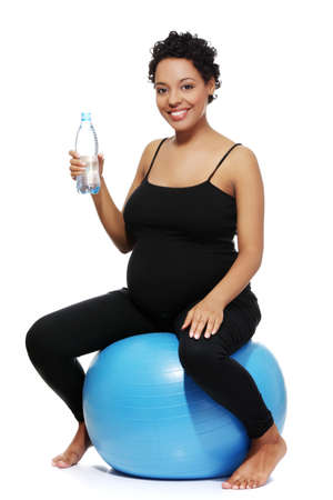 Full lenght portrait of a young smiling pregnant woman sitting on a blue ball, holding a bottle of water, isolated on a white background. photo