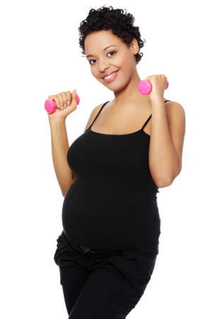 Portrait of a young smiling pregnant woman holding weights in her hands, isolated on a white background. photo