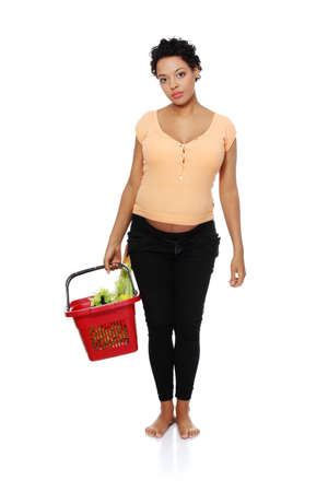 Full lenght picture of a pregnant woman carrying a shopping bascet, isolated on a white background. photo