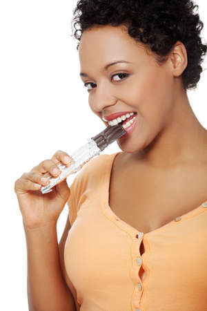 Portrait of a beautiful young woman eating a chocolate, smiling to the camera, over a white backgroung. photo