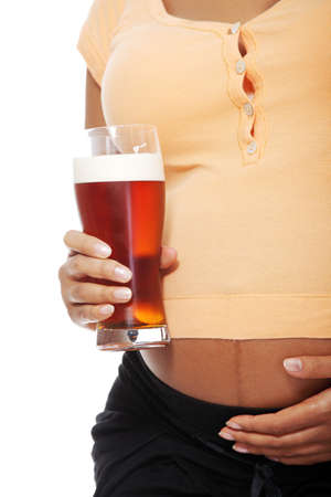 Belly closeup of a pregnant woman holding a glass alcohol next to her belly, over a white backgroung. photo