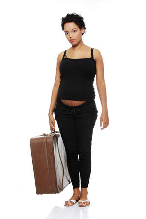 Full lenght front view of a sad pregnant woman holding a case. photo