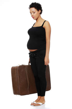 Full lenght site view of a sad pregnant woman holding a case. photo