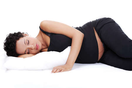 Portrait of a beautiful young pregnant woman while sleeping, isolated on a white background. Stock Photo - 12388303