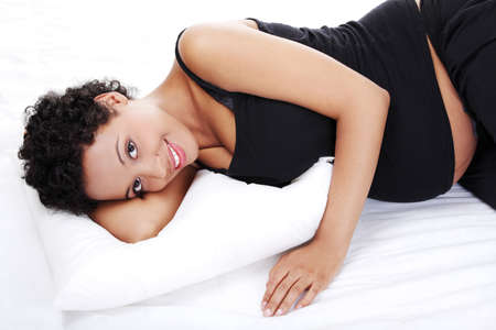 Portrait of a beautiful young pregnant woman while sleeping, isolated on a white background  photo