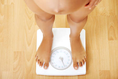 Pregnant woman standing on the scales - view from the top on the scales. photo