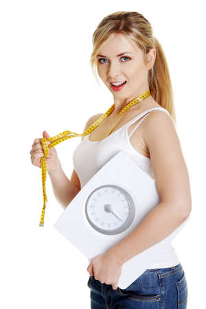 Woman with bathroom scale and measuring tape , isolated on white photo