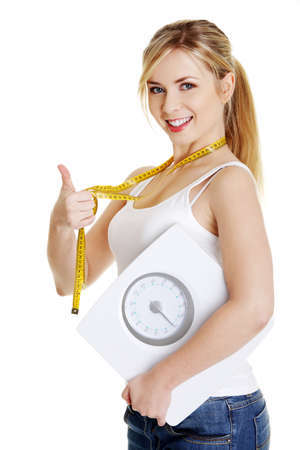 Woman with bathroom scale and measuring tape gesturing OK, isolated on white