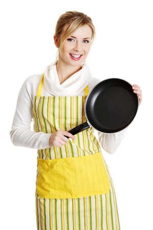 jasschort: Vooraanzicht portret van een lachende jonge blanke vrouw tiener gekleed in schort, die de pan, geïsoleerd op wit.