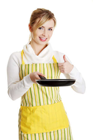 Front view portrait of a young smiling caucasian female teen dressed in apron, holding the frying pan,isolated on white.  photo