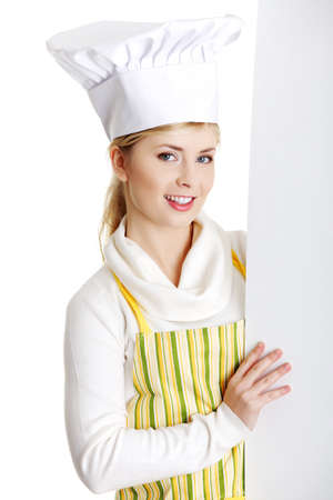 Happy woman cook or baker looking over paper sign billboard. Caucasian woman isolated on white background.