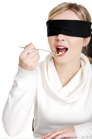 Pretty young blindfold woman holding spoon with pile of pills