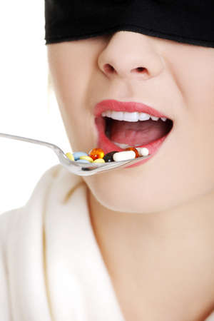 blindfold: Pretty young blindfold woman holding spoon with pile of pills
