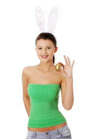 Young girl with easter bunny ears holding golden egg , isolated on white photo
