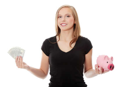 Happy teen holding a piggy bank and dollars, isolated on white background photo