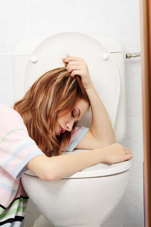 bulimia: Young teen woman vomiting in toilet