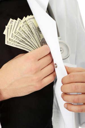 corrupt practice: Doctor hiding money into his pocket. Corruption concept