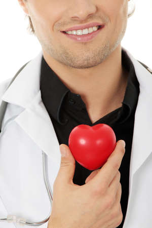 Handsome young male doctor holding heart shape toy photo
