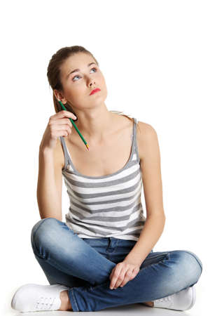 Front view portrait of a full length caucasian female teen sitting on a table, holding a pencil and looking up, on white.  Stock Photo - 13188550