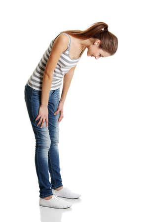 La muchacha adolescente mirando hacia abajo. Aislado en blanco