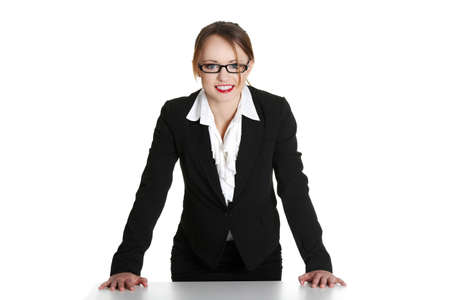 bossy: Portrait of beautiful successful businesswoman standing behind the desk. Isolated on white  Stock Photo