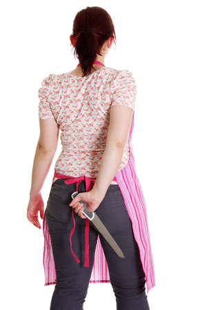 dangerous love: Casalinga in grembiule rosa con un coltello dietro la schiena. Isolato su bianco.