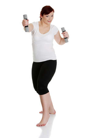 overweight people: Young woman during fitness time and exercising with dumbbells, isolated on white background