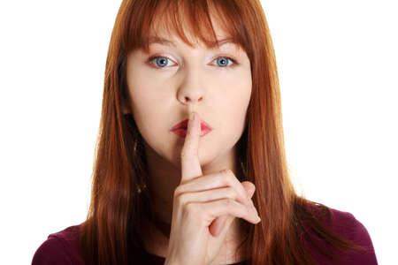discreto: Mujer joven que gesticula para la tranquilidad, aislado en fondo blanco Foto de archivo