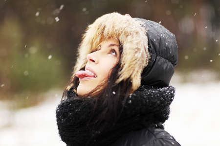 Happy beautiful woman playing outdoor, trying to catch snowflakes with her tongue photo