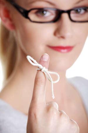 przypominać: Kobieta stara się pamiętać, co kawałek rundy ciąg palec miał jej przypomnieć, samodzielnie na białym tle.