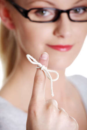 Woman trying to remember what the piece of string round her finger was meant to remind her of, isolated on white background.  photo