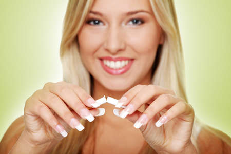Young beautiful blond smiling woman breaking cigarette