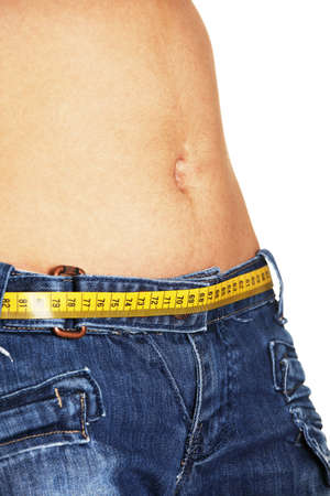 Weight control concept. Woman belly with measuring tape as a belt, isolated on white background Stock Photo - 15003463