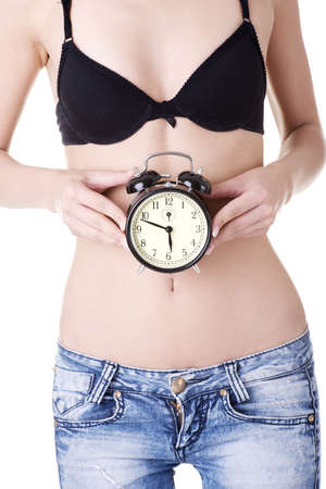 Beautiful fit woman with clock on belly photo